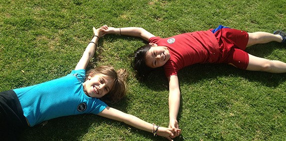 Image of two JAIS girls on the grass holding hands
