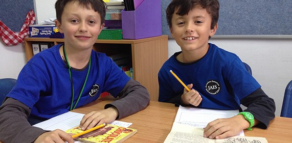 Image of two boys writing and smiling