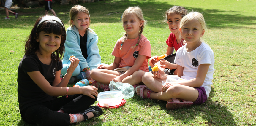 Image of JAIS elementary girls eating on the grass