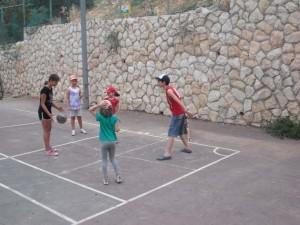Photo of five kids playing basketball at JAIS summer camp